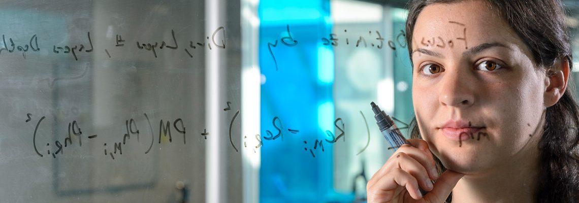Dr. Agnes Cseh schreibt mathemathische Formeln an eine Glastafel