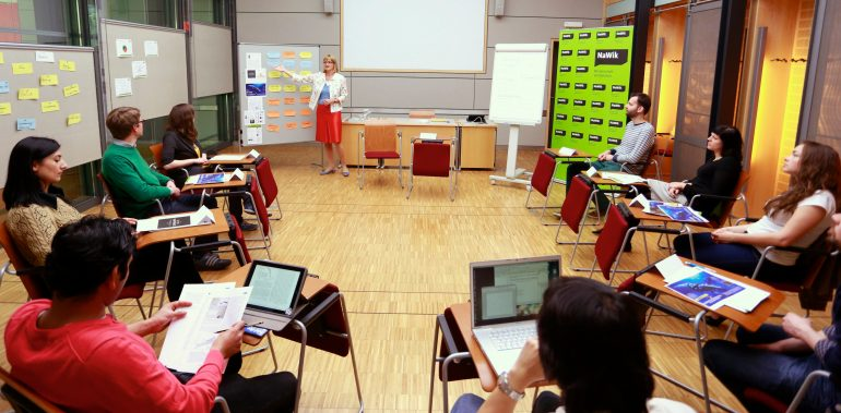 Teilnehmer des Workshops Wissenschaftskommunikation sitzen in einem Stuhlkreis, während eine Moderatorin Karteikarten an eine Pinnwand hängt.