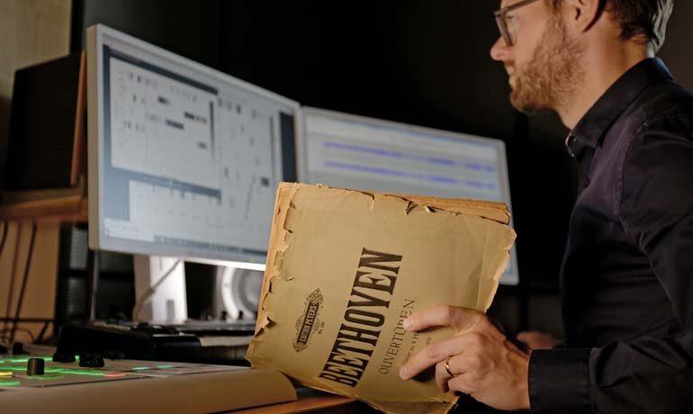 Christof Weiß arbeitet am Computer mit einem alten Beethoven-Notenheft.