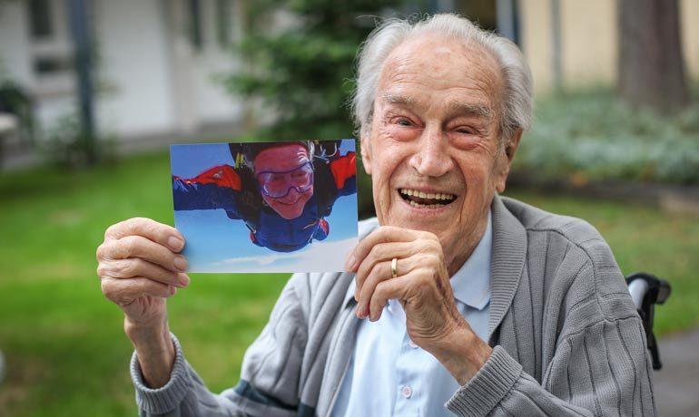 Ein Rentner zeigt ein Foto in die Kamera, das ihn beim Fallschirmsprung zeigt.